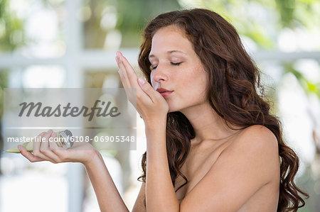 Woman smelling moisturizer