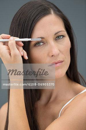 Portrait of a woman applying eyeliner
