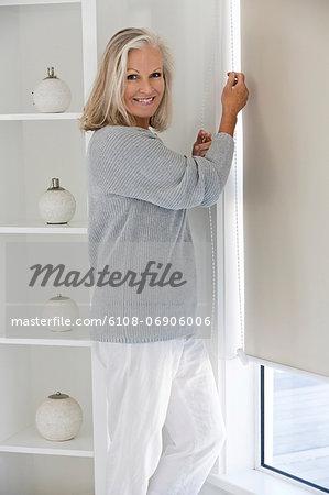 Woman adjusting window curtain
