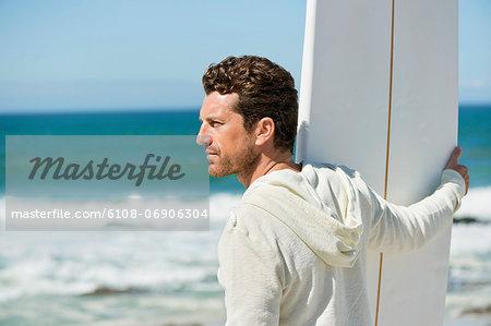 Man holding a surfboard on the beach