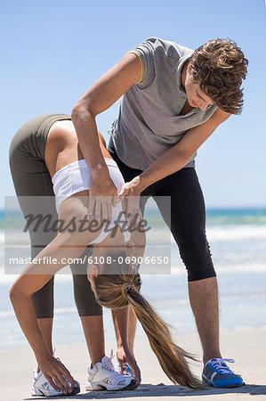 Man helping woman stretch at beach