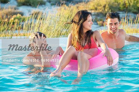 Three friends enjoying in a swimming pool on the beach