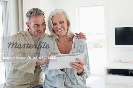 Smiling senior couple using a digital tablet