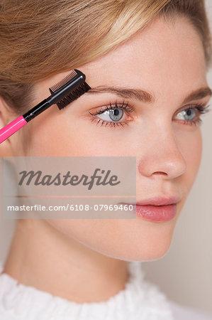 Beautiful woman brushing her eyebrow