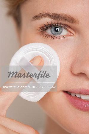 Beautiful woman applying powder puff