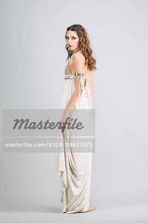 "Young woman standing in profile, wearing a beige dress ""Sanhadja"""
