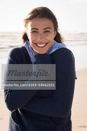 Beautiful young woman standing o the beach