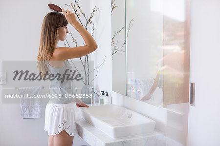 Woman combing hair in a bathroom