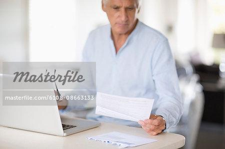 Senior man paying bills online on laptop