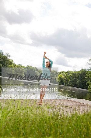 Pretty woman stretching by a lake