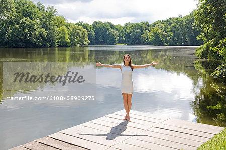 Pretty elegant woman stretching by a lake