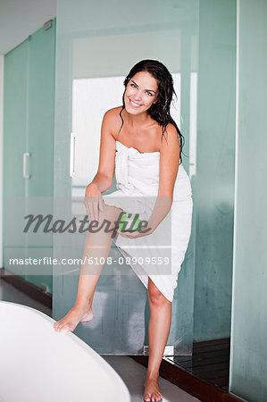 Brunette woman apliying moisturizer after the shower