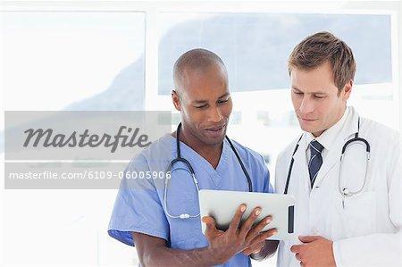 Standing doctors using tablet computer together