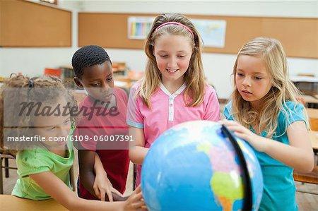 Elementary students exploring globe together