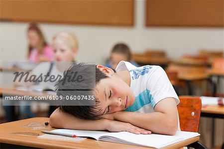 Schoolboy sleeping at his desk