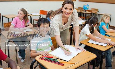 Smiling elementary teacher correcting students work