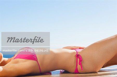 Woman enjoying sunny day lying on the pool edge