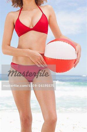 Woman in a bikini holds a beach ball against her hip
