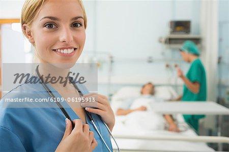blonde nurse smiling while touching a stethoscope stock photo