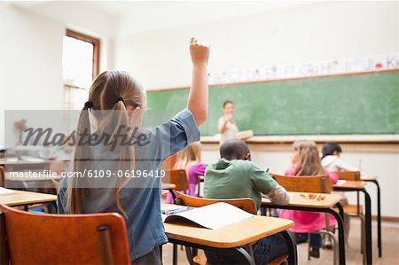 Back view of primary school student raising hand