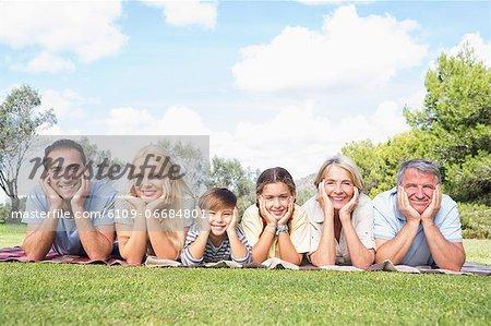 Cheerful multi-generation family lying on picnic blanket