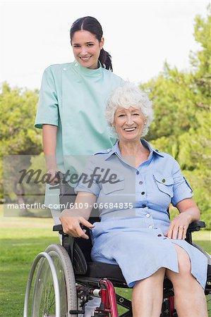 Portrait of nurse pushing elderly woman in wheelchair