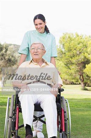 Nurse pushing elderly man through the park