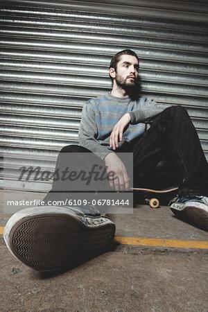 Skater sitting on his board taking a break
