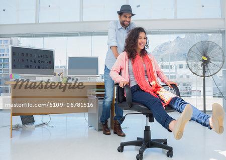 Photo editors having fun on an office chair