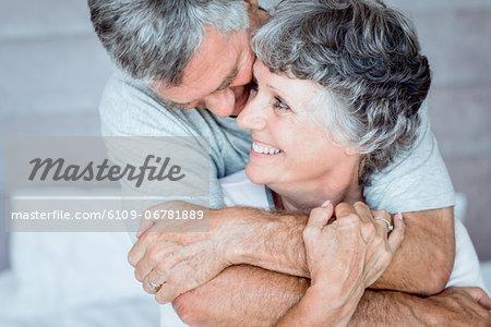 Mature man cuddling his wife