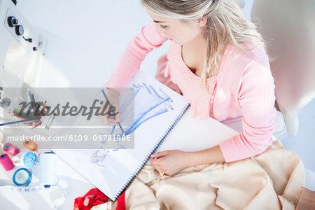 Blonde fashion designer drawing clothes