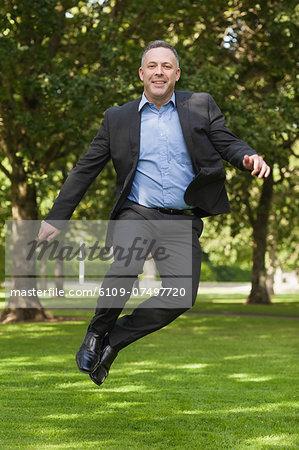 Joyful professor clicking his heels on campus at the university