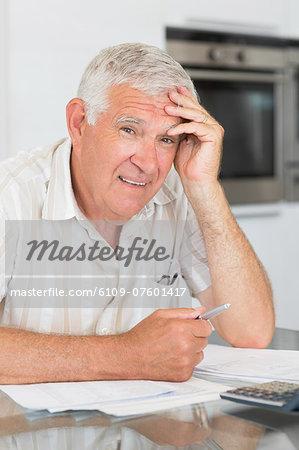 Worried senior man paying his bills