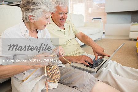 Senior couple sitting on floor knitting and using laptop