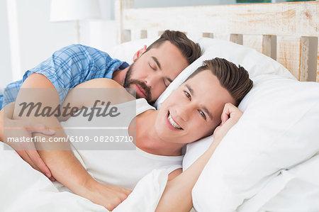 Homosexual couple lying on bed
