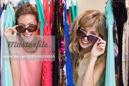 Friends wearing sunglasses between clothes racks
