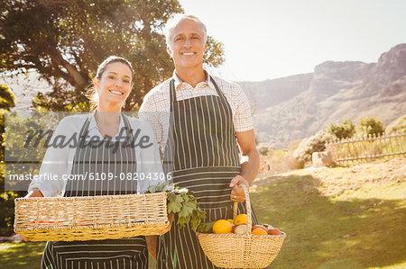 Smiling farmer couple holding a vegetable basket
