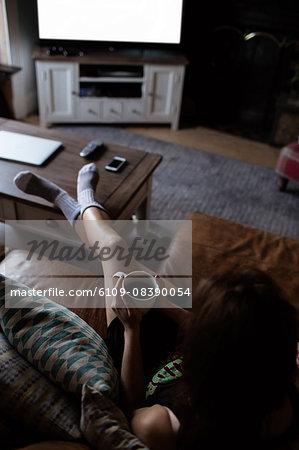 Young woman laying on the sofa holding mug