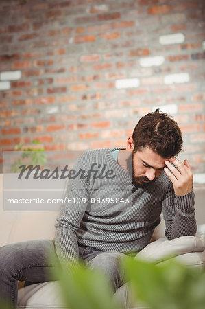 Sad man holding his forehead