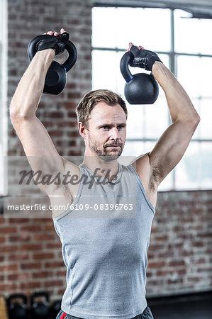 Fit focused man lifting kettlebells