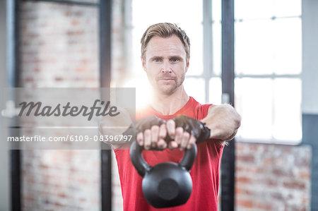 Muscular focused man lifting kettlebells