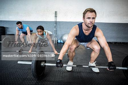Three muscular athletes liftings barbells