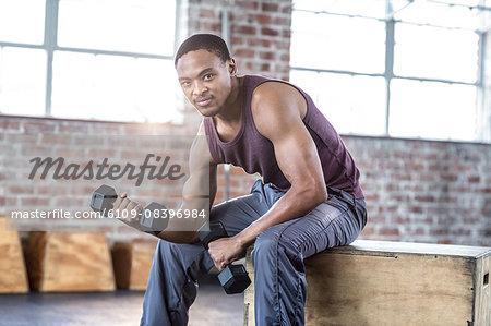 Smiling muscular man lifting dumbbell