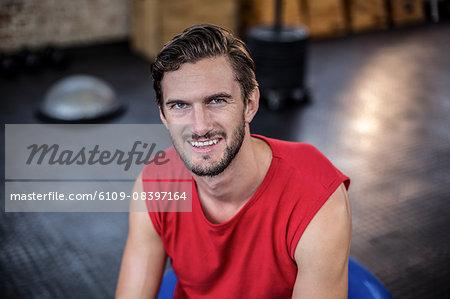 Smiling trainer sitting on medicine ball