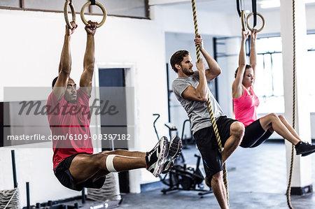 Athletes doing ring gymnastics and climbing rope