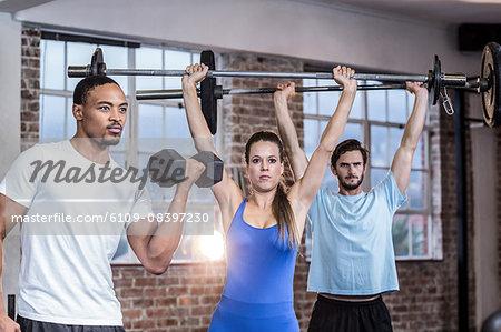 Three muscular athletes lifting weights