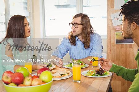 Creative business people talking while having breakfast