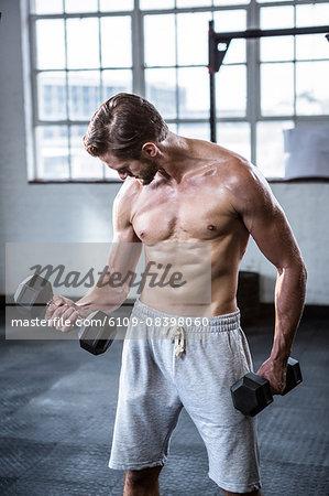 Fit shirtless man lifting dumbbells