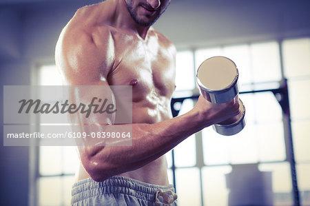Fit shirtless man lifting dumbbell