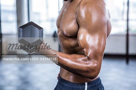 Fit man lifting heavy black dumbbells